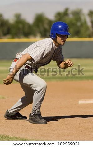 Young baseball player ready to run at second base - stock photo