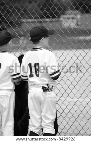 young baseball player watching the game while waiting for his turn to bat - stock photo