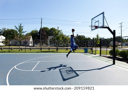 Young basketball player driving to the hoop for a high flying slam dunk. - stock photo