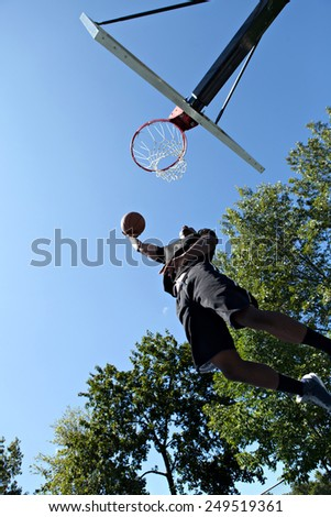 Young basketball player driving to the hoop for a high flying slam dunk - stock photo