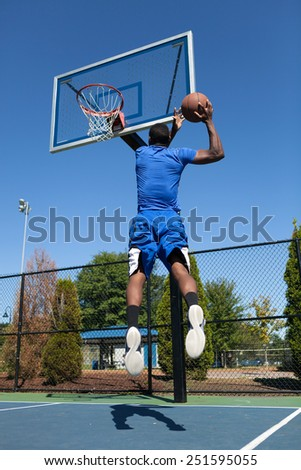 Young basketball player driving to the hoop for a high flying slam dunk.