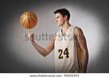 Young basketball player holding a basketball on his finger - stock photo