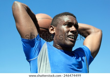 Young basketball player in his early twenties posing with the ball held behind his head. - stock photo