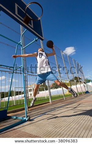 Young basketball player is jumping to the basket. - stock photo