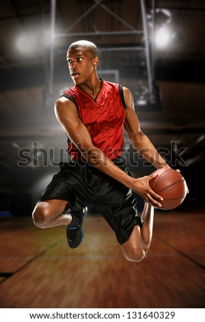 Young Basketball player jumping inside a court - stock photo