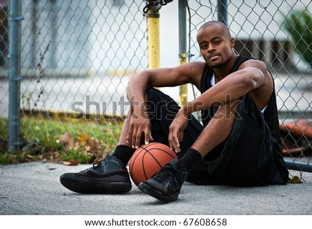 Young basketball player seated in the street looking at camera. - stock photo