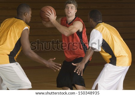Young basketball player with ball being blocked by opponents - stock photo