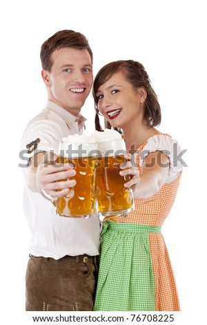 Young Bavarian couple in love hold Oktoberfest stein saying cheers.Isolated on white background. - stock photo