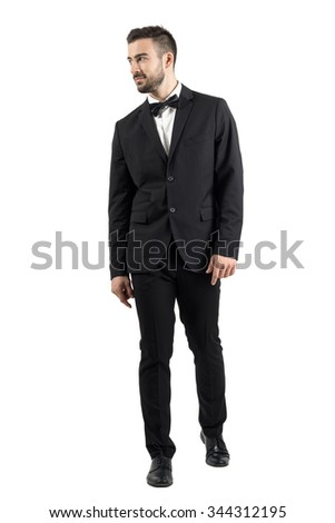 Young beaded man in tuxedo with bow tie walking towards the camera looking away. Full body length portrait isolated over white studio background. - stock photo
