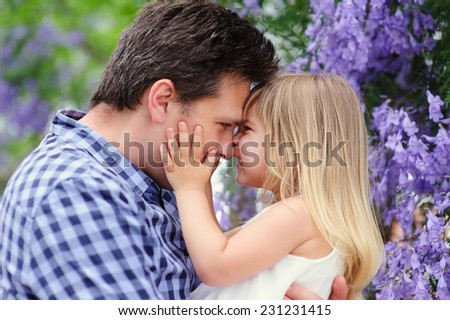 Young beaitiful father and his cute daughter love in blooming jacaranda garden - stock photo