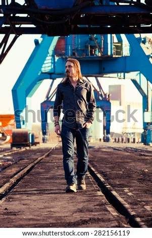 young beard man in shirt and jeans walk in port - stock photo