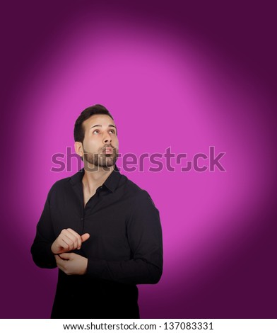 Young bearded businessman buttoning his shirt button on purple background - stock photo