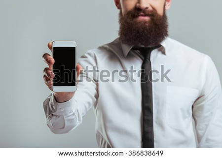 Young bearded businessman in classic white shirt is showing a mobile phone and smiling, on a gray background, close-up - stock photo