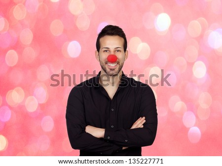 Young bearded businessman with clown nose on a over pink and lights background - stock photo