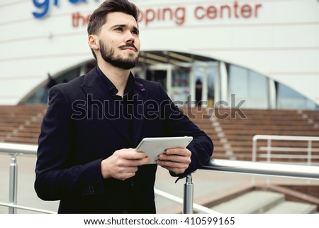Young bearded businessman writting business e-mail using his tablet pc. - stock photo