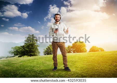 Young bearded Caucasian man in casual clothes is standing on a sunny lawn with headphones on his head and phone in hand and showing a thumb up gesture - stock photo