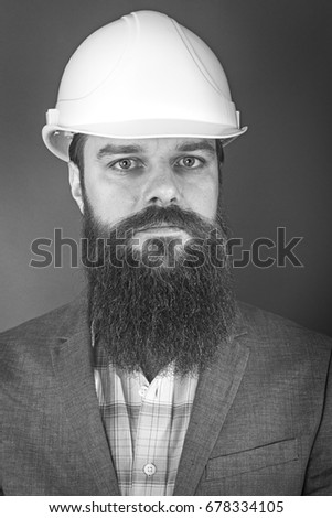 Young bearded engineer with helmet standing over gray background