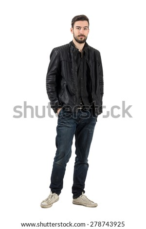 Young bearded fashion model looking at camera in leather jacket. Full body length portrait isolated over white background.
