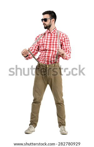 Young bearded hipster pulling suspenders looking away.  Full body length portrait isolated over white background.  - stock photo