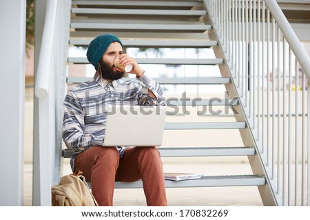 Young bearded hipster student using computer and drinking coffee at university campus - stock photo