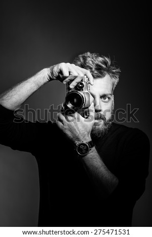 Young bearded man holding retro camera against black background. Confident  photographer shooting at studio. Black and white photography. - stock photo