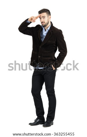 Young bearded man in corduroy coat saluting at camera. Full body length portrait isolated over white studio background.