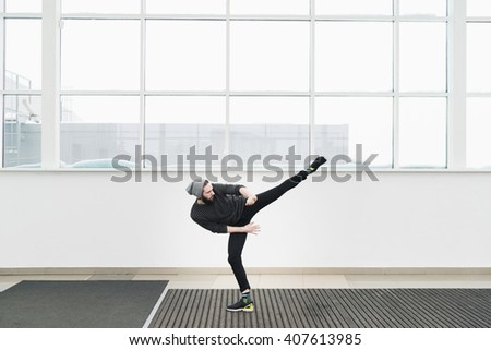 Young bearded man in motion against of window