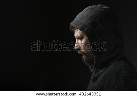 Young bearded man in studio with hood - stock photo