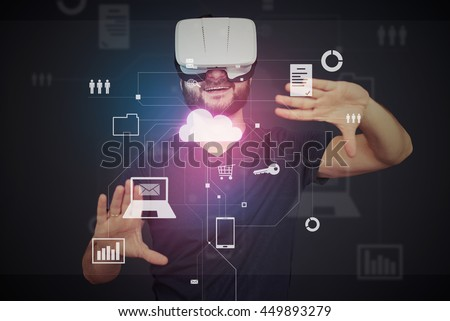 Young bearded man in VR-headset is surrounded by virtual data on interactive touch screen over dark background - stock photo