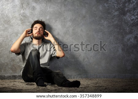 Young bearded man listening music with headphones on grey wall background - stock photo