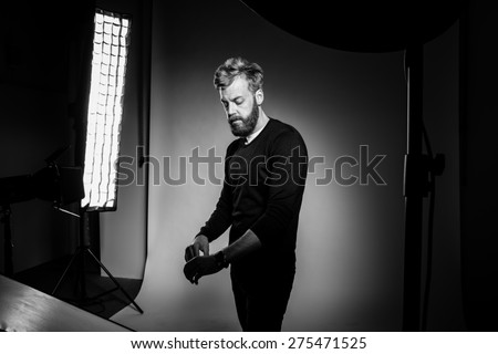 Young bearded man posing against black background at photo studio. Black and white photography. - stock photo