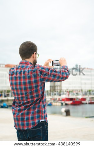 Young bearded man taking a picture with his phone outdoors at a pleasure harbour - stock photo