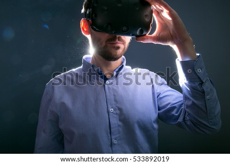 young bearded man using VR virtual reality glasses headset. art light photo. dark grey background
