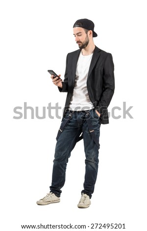 Young bearded man with backward hat using mobile phone device. Full body length portrait isolated over white background.  - stock photo