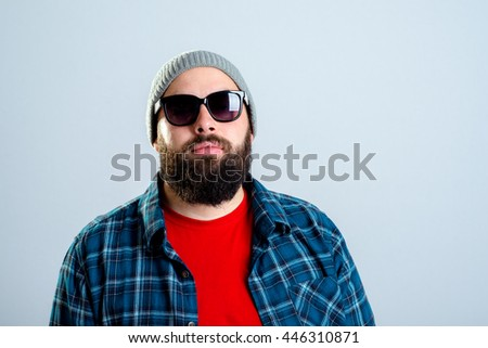 young bearded man with baseball cap and sunglasses is looking angry - stock photo