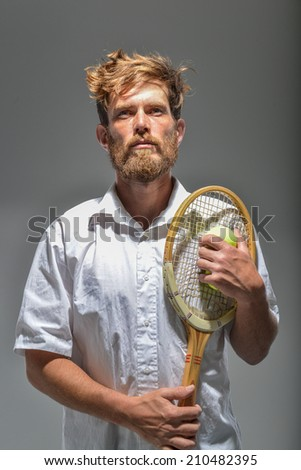 young bearded man with tennis racket and yellow ball - stock photo