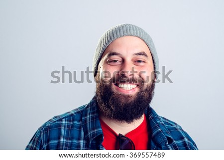 young bearded man with woolen cap is smiling - stock photo