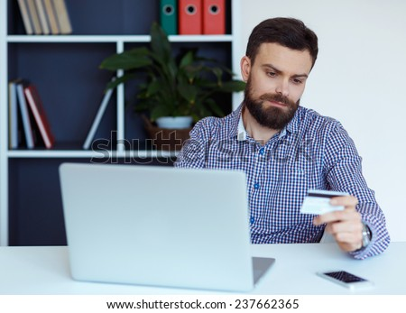 Young bearded man working on a laptop in the office - pays by credit card online shopping - stock photo