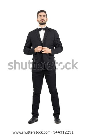 Young bearded wealthy man buttoning tuxedo with bow tie. Full body length portrait isolated over white studio background.