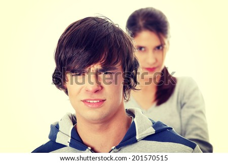 Young beaten up caucasian man standing in front of angry young woman. Couple fight. - stock photo