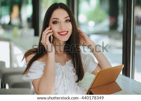 Young beatiful brunette woman with tablet in cafe, shot through  - stock photo