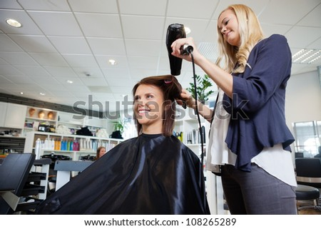 Young beautician blow drying hair of customer after a haircut
