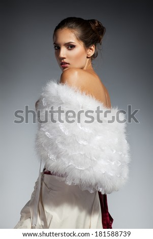 Young beautiful adult girl wearing elegant wedding dress. Studio shot - stock photo