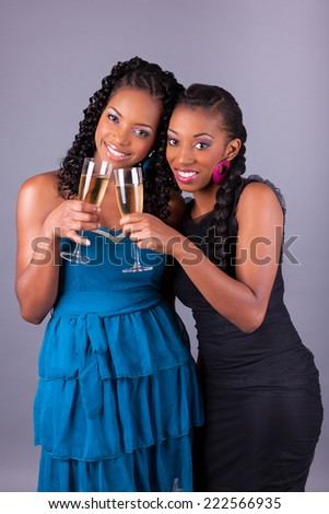 Young beautiful African American womans holding a glass of champagne - stock photo