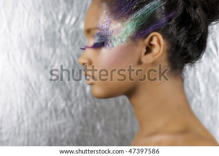 Young beautiful African woman with art make-up on a silver background - stock photo