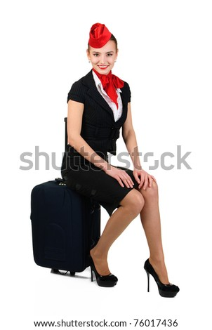 young beautiful airhostess sitting on bag - stock photo