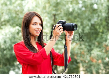 Young beautiful amateur female photographer with new dslr camera in the park. - stock photo