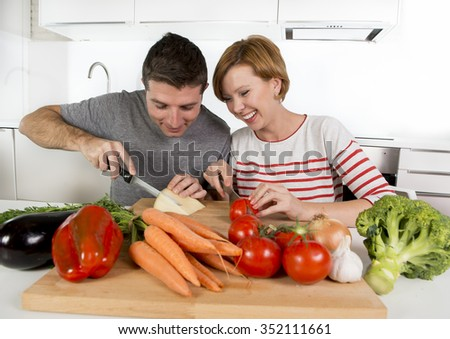 young beautiful American couple working at home kitchen  preparing  vegetable salad together smiling happy in husband and wife cooking team and  healthy fresh food concept  - stock photo