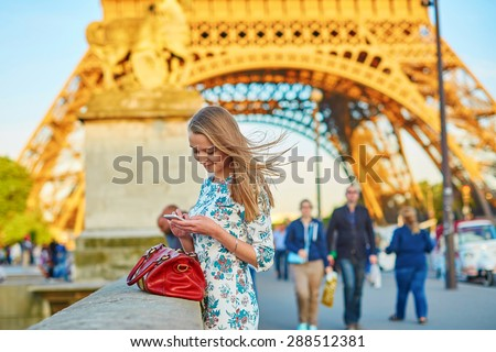 Young beautiful and elegant Parisian woman in blue dress near the Eiffel tower in Paris, checking her mobile phone - stock photo