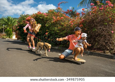 Young, beautiful and happy parents ride by skateboards with the baby. They are accompanied by a cute dog - stock photo